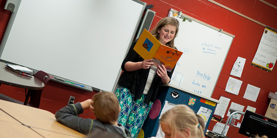Teacher reading in front of a large audience of kids, smiling to herself