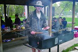 Man grabbing a hot dog at a picnic